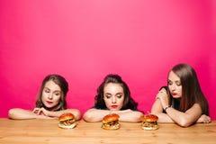 Trois filles tristes sur le régime regardant des hamburgers sur la table Images stock