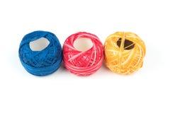 Trois fils de couture colorés sur un fond blanc Image stock