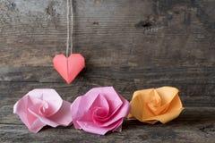 Trois fleurs d'origami et un coeur Images stock