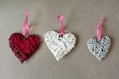 Trois formes en bois de coeur sur le tissu de toile Photo stock