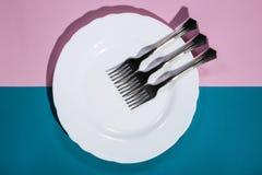 Trois fourchettes d'un plat blanc sur coloré Image libre de droits