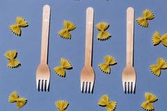 Trois fourchettes parmi des macaronis d'isolement sur le fond bleu photographie stock libre de droits