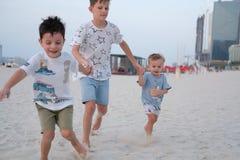 Trois frères courent sur la plage, tenant des mains images libres de droits