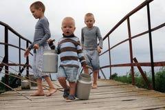 Trois frères sont venus au pont dans le village à travers la rivière pour pêcher mais ont à la place couru le long du pont de l'e Photo stock