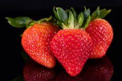 Trois fraises d'isolement sur le noir Images stock