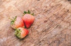Trois fraises fraîches sur le vieux fond en bois Images stock
