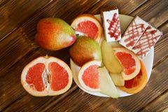 Trois g?teaux de biscuit, tranches de pamplemousse et poires se situent dans un plat blanc sur une table en bois faite de panneau image libre de droits