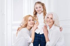 Trois générations de la famille se reposant ensemble à la maison Image stock