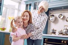 Trois générations des femmes collant dans la cuisine Photo stock