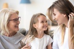 Trois générations des femmes ont l'amusement à la maison ensemble photos stock