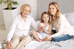 Trois générations des femmes s'asseyant sur un lit Photos libres de droits