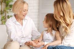 Trois générations des femmes tenant des mains ensemble Image libre de droits