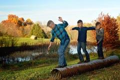 Trois garçons équilibrant sur un ponceau images stock