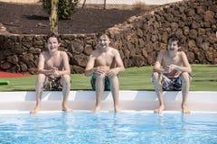Trois garçons de l'adolescence s'asseyant à une piscine Photographie stock