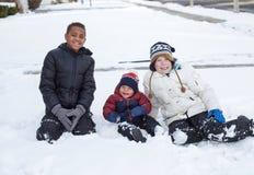Trois garçons divers mignons jouant ensemble dans l'extérieur de neige images stock