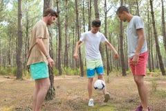 Trois garçons jouant le football dans la forêt Image stock