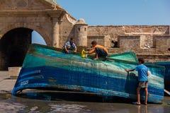 Trois garçons lavent le bateau de pêche bleu près de la Médina photographie stock