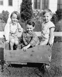 Trois garçons s'asseyant dans un chariot et un sourire de poussée (toutes les personnes représentées ne sont pas plus long vivant Image libre de droits