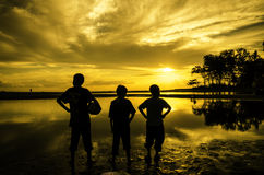 Trois garçons se tenant vers le soleil pendant le coucher du soleil de lever de soleil Photos libres de droits
