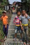 Trois garçons sur un pont suspendu Images stock
