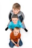 Trois garçons sur un fond blanc Photos stock