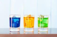 Trois genres de boissons alcoolisées dans des verres à liqueur dessus Photographie stock libre de droits