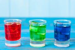 Trois genres de boissons alcoolisées dans des verres à liqueur dessus Images libres de droits