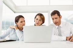 Trois gens d'affaires à l'aide de l'ordinateur portable image libre de droits