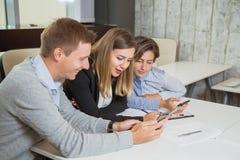 Trois gens d'affaires d'équipe de téléphones portables et causerie de prise Photo stock