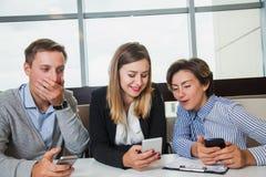 Trois gens d'affaires d'équipe de téléphones portables et causerie de prise Photos stock
