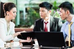 Trois gens d'affaires discutant le plan dans le bureau photographie stock libre de droits