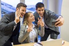 Trois gens d'affaires font un Selfie heureux dans le bureau Photos stock