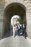 Trois gens d'affaires marchent par la porte de la ville murée, Avila Espagne, un vieux village espagnol castillan Photos stock