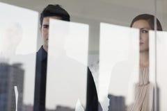 Trois gens d'affaires se tenant et regardant de l'autre côté d'un mur de verre images stock