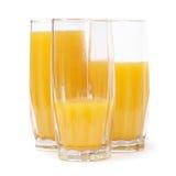 Trois glaces avec le jus d'orange Photos stock