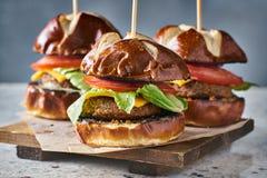 Trois glisseurs d'hamburger de vegan avec des petits pains de bretzel photo stock