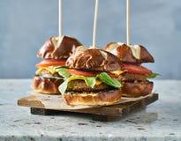 Trois glisseurs d'hamburger de vegan avec des petits pains de bretzel images stock