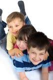 Trois gosses heureux jouant sur l'étage Photo stock