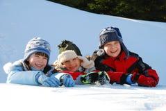 Trois gosses jouant dans la neige Image stock
