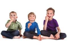 Trois gosses mangeant des bonbons Images stock
