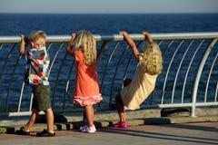 Trois gosses regardant à l'extérieur à la mer Images libres de droits