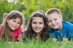 Trois gosses sur l'herbe Photos libres de droits