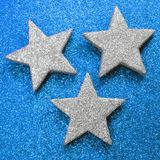 Trois grandes étoiles d'argent sur le fond scintillant bleu lumineux photo libre de droits