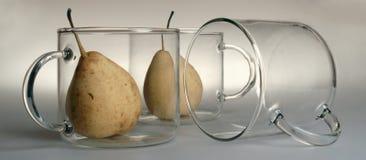 Trois grandes tasses en verre transparentes rondes avec de grandes poignées : un est tourné à l'envers et se trouve de son côté,  Image stock