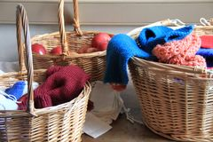 Trois grands paniers en bois ont rempli de pommes, d'aiguilles de tricotage et de fil coloré Image libre de droits
