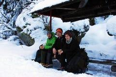 Trois grimpeurs se reposant sur un banc en montagnes de Retezat, Roumanie Photos stock