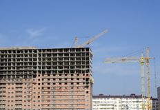 Trois grues de construction parmi des bâtiments en construction Photos libres de droits