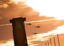 Trois hélicoptères d'Apaches volant après une tour avec des nuages Photos stock