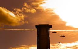 Trois hélicoptères d'Apaches volant après une tour avec des nuages Photographie stock libre de droits