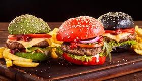 Trois hamburgers asiatiques colorés avec des pommes frites photo libre de droits